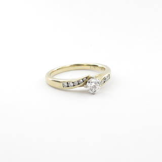 18ct yellow and white gold diamond solitaire cross over style ring with shoulder diamonds